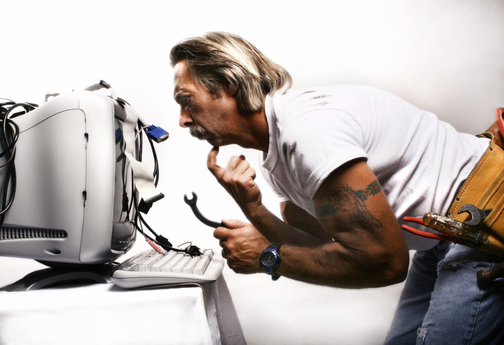 Businessman trying to fix his computer (upgrade business technology)